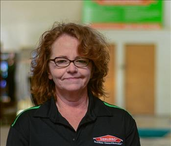 Woman with glasses and curly hair wearing a SERVPRO shirt